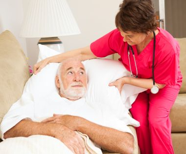 Home health nurse fluffs an elderly patient's pillow.